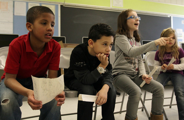 From left, Bentley Elementary School second graders Ellison Toribio, Radhoen Rena, and Jimena Pueyo listen to instructor Ann Tarascio as she asks questions on the first day of an after school program where students stay after school for homework help. David Le/Salem News