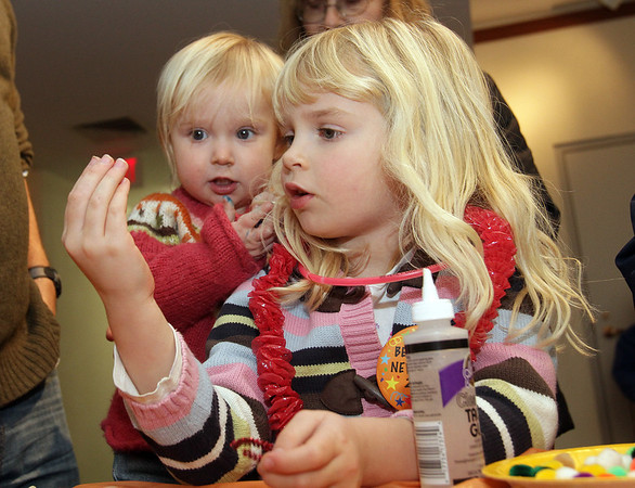 Beverly: Cate, 5, and Reagan Miller, 1, of Ipswich, examine some arts and crafts pieces in Beverly Public Library on New Year's Eve. David Le/Salem News