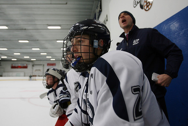 St. John's Prep senior captain Nick Pandelena (21), watches the action on ice while his coach ____________ yells out instructions. David Le/Salem News