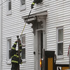 Peabody: A fireman leaning out the window of the second story of 5 Hancock St. in Peabody is handed up a fire hose by another firefighter on the ground. David Le/Salem News