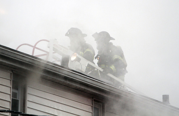 Peabody: Two Peabody firefighters work through thick smoke to try and break through the roof of 5 Hancock St., the site of a 3-alarm blaze on Friday afternoon.David Le/Salem News