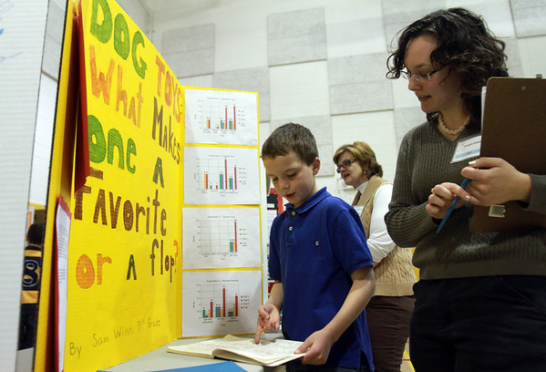 Ayers Ryal Side Elementary School third grader Sam Winn, left, talks about his science fair project about dog toys with evaluator Elisabeth Antanavichon Wednesday afternoon. David Le/Staff Photo