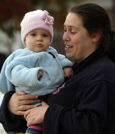 Sophia Filtrante, of Beverly, and her Kelly, 10 months, wait for the annual Beverly Holiday parade to start on Sunday morning. David Le/Salem News