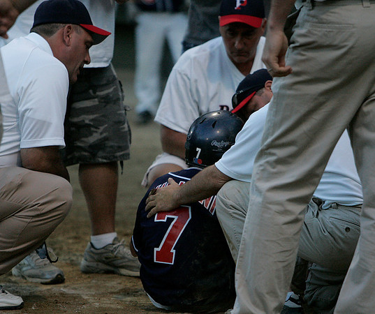 Beverly: Coaches from both Beverly West and Peabody West tend to Peabody thirdbaseman John Villani after a scary moment when Villani was hit square in the face by a pitch. Photo by David Le/Salem News
