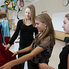 Ipswich High School seniors Alex Sulkin, left, Paige Sirois, center, and Morgan Riddle, right, look through some of the prom dresses at their fundraiser selling used prom dresses for the Lazarus Cancer Foundation. David Le/Salem News