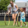 Annie Swanson, 4, of Salem, and her babysitter Marlena Udden, also of Salem, race hoops across the lawn at the House of 7 Gables on Thursday afternoon as part of the Salem Heritage Days festivities. David Le/Staff Photo