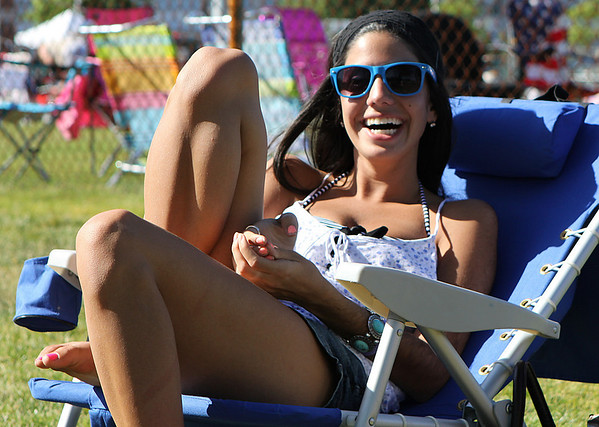 Danvers: Kristine Kapoll, of Danvers catches some sun and chats with her friends while waiting for festivities to start at the Danvers Fireworks Festival on Saturday afternoon at Plains Park in Danvers. Photo by David Le/Salem News