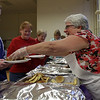 Cathy Silva, of Peabody, right, hands out pancakes during the pancake dinner portion of St. Thomas the Apostle Church's Mardi Gras celebration. David Le/Staff Photo