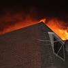 Smoke and fire billowed out of the top of an apartment complex located in Beverly on Folley Pond Road on Wednesday night. David Le/Salem News