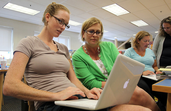 Carlton School E1 teachers Kristen Rodgers, left, and Lisa Critch, right, work together to learn a new technology program for the upcoming academic year. David Le/Staff Photo