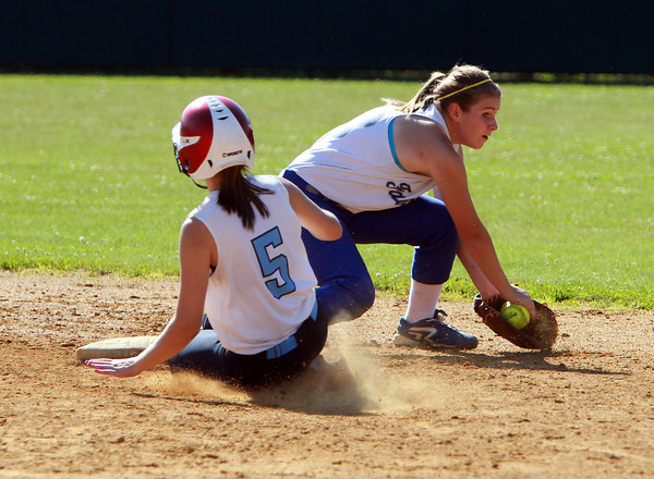Danvers High School shortstop Brittany Dougal receives a throw from right fielder Erica Fleming, but is too late to tag out Dracut's Shannon Ramirez. David Le/Staff Photo
