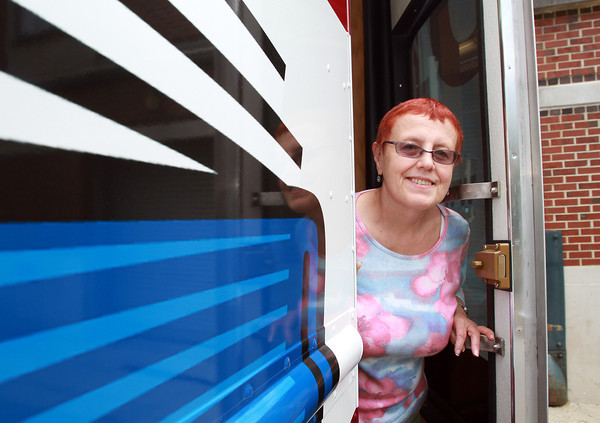Linda Caravaggio, BookMobile Librarian for the past 25 years stands in the doorway of their brand new BookMobile which has arrived at Beverly Public Library. David Le/Staff Photo