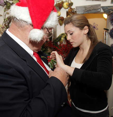 Liza Tosi, of Marblehead, right, pins a bit of holly onto the jacket of singer Jack Dowd, of The Village Voices at Flores Mantilla on Sunday. David Le/Salem News