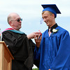 "Danvers High School teacher James Lombard presents senior Jon Wright with a ""suprise"" Hershey's Kiss at the end of his Graduation address on Saturday afternoon. David Le/Staff Photo"