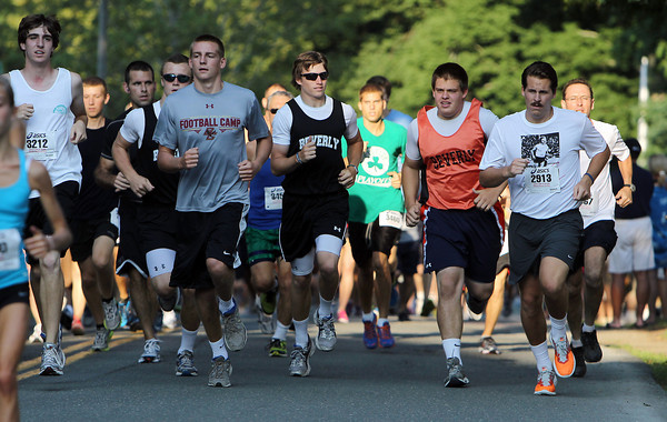 A large field of runners sprint down Ober St. in Beverly alongside Lynch Park at the start of the 45th Annual Homecoming Road Race on Thursday evening. David Le/Staff Photo