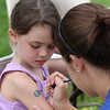 Danvers: Makayla Greene, age 7 of Beverly patiently waits as Emily Beehen a sophmore member of the Danvers High School marching band carefully paints a design on her arm at Endicott Park Day on Saturday afternoon in Danvers. Photo by David Le/Salem News