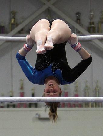 Danvers gymnast Aimee LeBlanc hangs upside-down on the bars on Friday night. David Le/Salem News