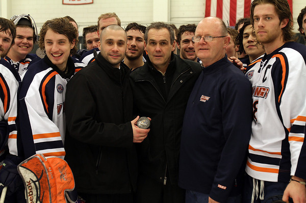 Salem State Men's Hockey Head Coach Bill O'Neill, center, is surrounded by his team after he recorded his 500th win as head coach of the Vikings. David Le/Staff Photo