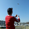 Tim Justice, of Salem, enjoys the beautiful March weather as he flies a kite at Pickering Wharf in Salem on Tuesday afternoon, David Le/Staff Photo