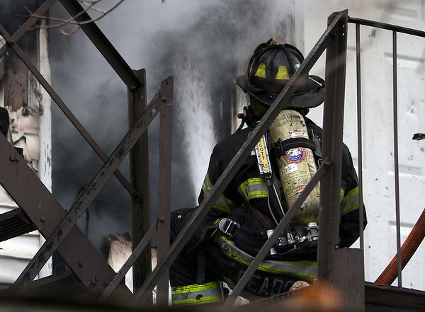 Peabody: A Peabody firefighter works to spray down the second floor of 5 Hancock St. on Friday afternoon. David Le/Salem News