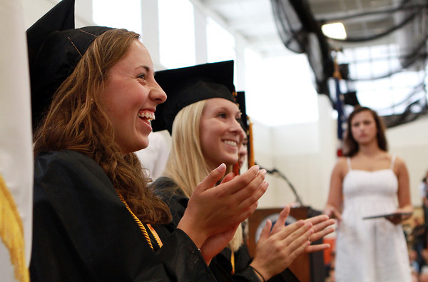 Beverly High School Co-Valedictorians Erin Silvestri, left, and Emily Boches, right, cheer on classmates as they walk across the stage and receive their diplomas on Sunday afternoon. David Le/Staff Photo