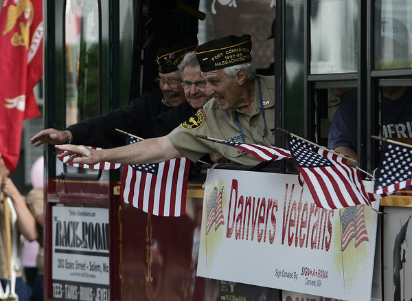 A few Danvers Veterans wave out the window of an escort trolley during the Danvers Memorial Day parade. David Le/Staff Photo