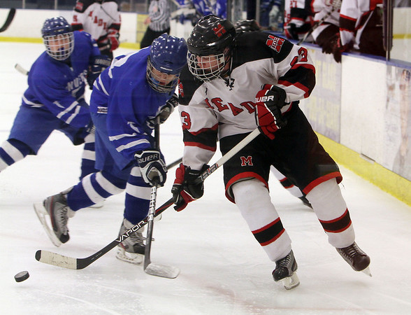 Marblehead's Austin Haley (23) right battles for a puck with Danvers' Joe Strangie. David Le/Salem News