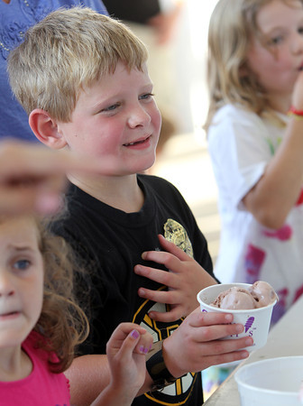 Ryan Corcoran, 6, of Beverly, smiles as he waits to be served some chocolate fudge for his ice cream sundae at the Beverly Homecoming Ice Cream Social on Monday evening. David Le/Staff Photo