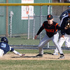Peabody's Casey Grenier (3) dives back to first base ahead of the tag from Beverly first baseman Kevin Cuneo, right. David Le/Staff Photo