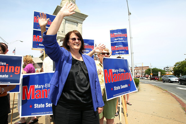State Senate candidate Mary-Ellen Manning waves to cars in Peabody Square on Saturday afternoon. David Le/Staff Photo