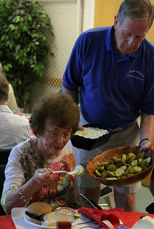 Danvers: Larry Crowley, right of the Danvers Kiwanis Club, offers Joan Geiger toppings for her burger at the Senior Citizen Lunch held at the Danvers Senior Center on Tuesday afternoon. Photo by David Le/Salem News
