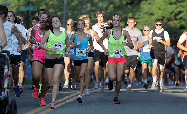 From left, Nicole Demars, of Beverly, Carly Curcuru, of Gloucester, and Keely Higgins of Beverly, pass Lynch Park at the start of the 45th Beverly Homecoming Road Race on Thursday evening. David Le/Staff Photo