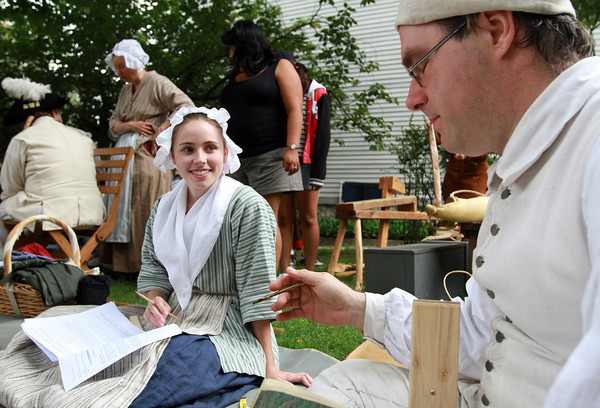 Re-Enactor Mary Asson, left, smiles as she talks with fellow re-enactor Mark Nowacki, right, about ciphers she was working on outside the Witch House Museum on Essex St. in Salem on Saturday morning. David Le/Staff Photo