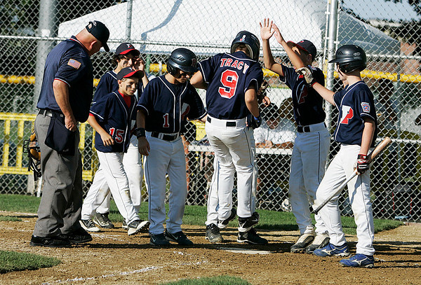 Norwood: Peabody West hitter Matt Tracy jumps onto home plate and into the wait arms of his teammates after he hit a moon-shot home run in the bottom of the fifth inning to extend Peabody West's lead over Newton West to 5-1. Peabody West ended up winning the game by the same score in the opening game of the Massachusetts Final Four Little League Championship on Thursday afternoon at Kelly Field in Norwood. Photo by David Le/Salem News