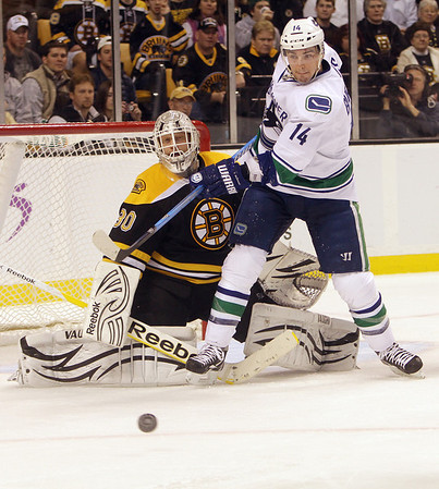 Bruins goalie Tim Thomas gets tangled up with Vancouver forward Alex Burrows as the puck deflects away. David Le/Salem News