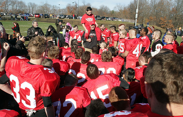Marblehead head coach Jim Rudloff, center, gives a speech to his team after they defeated Swampscott 21-7 on Thanksgiving morning David Le/Salem News
