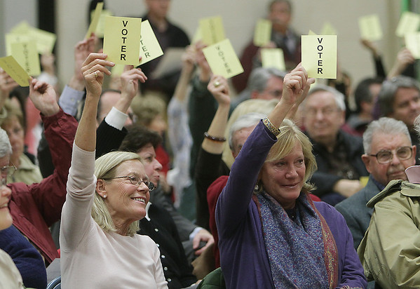 """Paula Shorts, left, and Paula Jerome, both of Wenham, raise their """"voter"""" cards to approve a liquor license for the Wenham Tea House on Wednesday night. David Le/Staff Photo"""