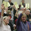 "Paula Shorts, left, and Paula Jerome, both of Wenham, raise their ""voter"" cards to approve a liquor license for the Wenham Tea House on Wednesday night. David Le/Staff Photo"