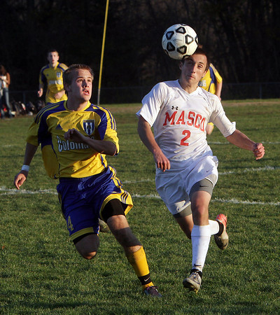 Masco's Chad Burke (2) heads the ball foward while being pursued by Acton-Boxborough's Ross Schulman (4) right. David Le/Salem News