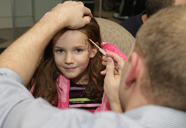 Beverly: Bridget Ayles, 5, of Beverly, smiles as she gets her face painted inside Beverly Cooperative Bank by Jeff Eldridge, of Danvers, on New Years Eve, David Le/Salem News