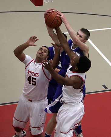Danvers guard Nick Bates (top) grabs a rebound over Salem's Jared Louf-Woods (45) and Davonte Holloway (23). David Le/Salem News