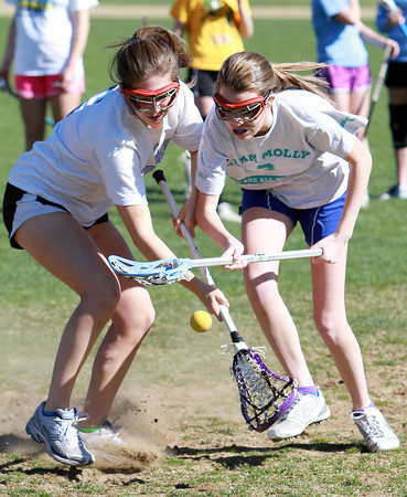 Danvers' Reagan Doyle, right, and Cate Raftery, left, battle for a ground ball at practice on Tuesday afternoon. David Le/Staff Photo