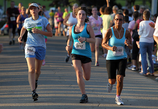 Three runners cross the finish line of the 45th Annual Beverly Homecoming Race on Thursday evening at Lynch Park. David Le/Staff Photo