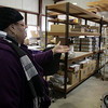 Donna McKenzie, Office Manager for the St. Joseph's Food Pantry points to the empty shelves in the storage room. Their government support funds have been cut from 7,000 lbs to 2,000 lbs and they are in need of financial donations to keep serving as many families as they do now. David Le/Salem News