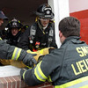 "Beverly Fire Captain Kevin Smith, right, shows the proper technique on how to carry a person out a window and onto a ladder during ""Rapid Intervention Training"" at the West Building at Endicott College on Saturday. David Le/Salem News"
