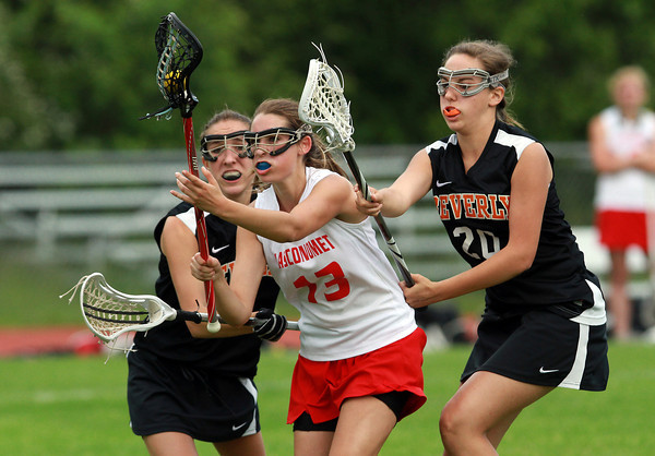 Masco attackman Rachel Rogal, center, splits through the defense of Beverly's Katie Pietrini, left, and Katie Ball, right, and drives to the net for a score. David Le/Staff Photo
