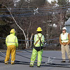 Peabody Municipal Light Workers wait for assistance to clear wires that fell in the middle of Herrick Road after an unmarked utility van stuck a telephone pole, snapped it in half, and dragged wires down into the street. David Le/Salem News