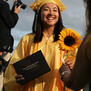 Bishop Fenwick graduate Colleen Chiu gets a sunflower after crossing the stage and receiving her diploma on Friday evening. David Le/Staff Photo