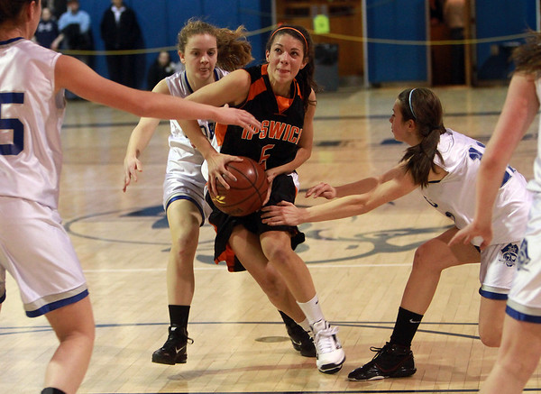 Ipswich freshman point guard Masey Zegarowski (5) center, drives to the lane while surrounded by Bedford defenders. Zegarowski and the Tigers defeated the Buccaneers to advance to the D3 North Final on Saturday in Lowell. David Le/Staff Photo