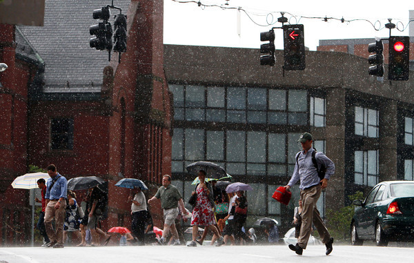 Travelers hurry across Bridge Street in downtown Salem in the pouring rain on Wednesday afternoon. David Le/Staff Photo
